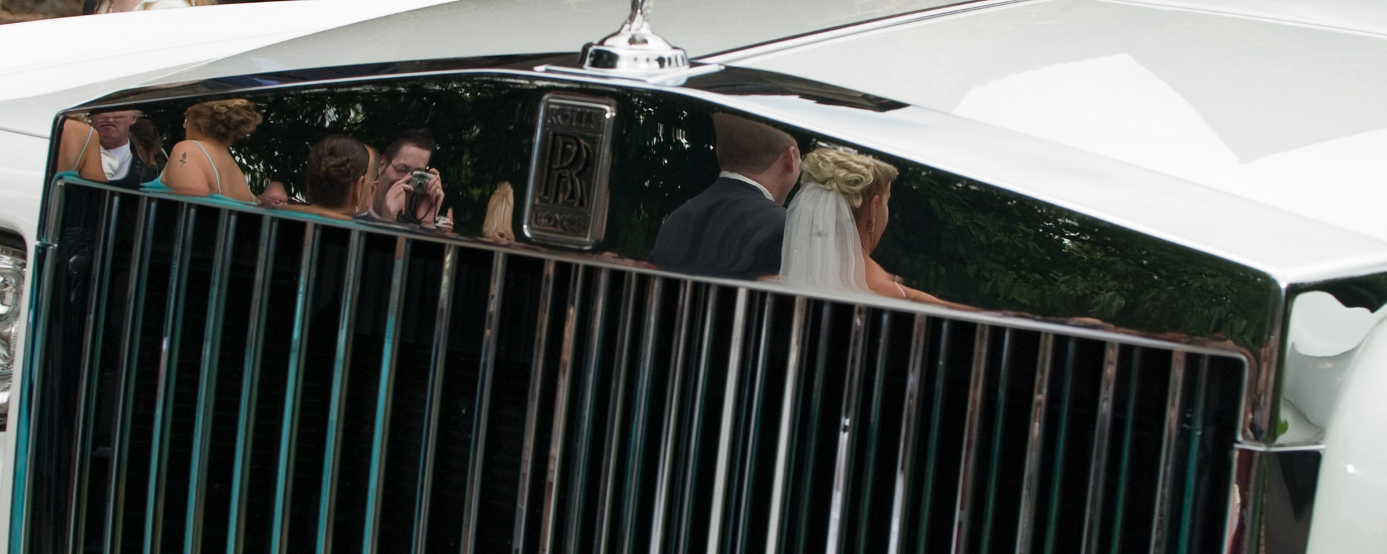 Reflection of bride and groom in Rolls Royce